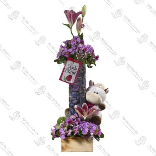 Arreglo floral lila, con peluche en jarrón de cristal