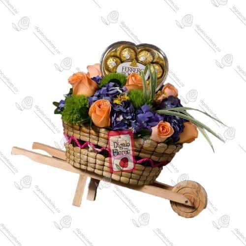 Carretilla de flores acompañado de chocolates